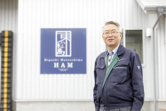 工場の前に立つオイタミート代表取締役及田賢治の写真